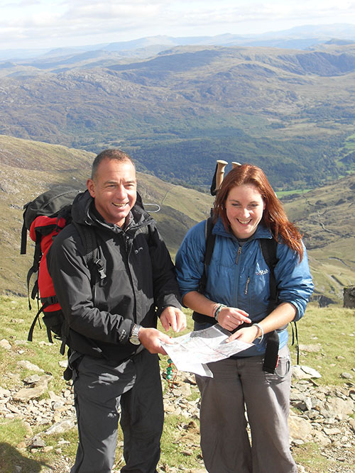 Two people studying a map during a navigation course in Snowdonia